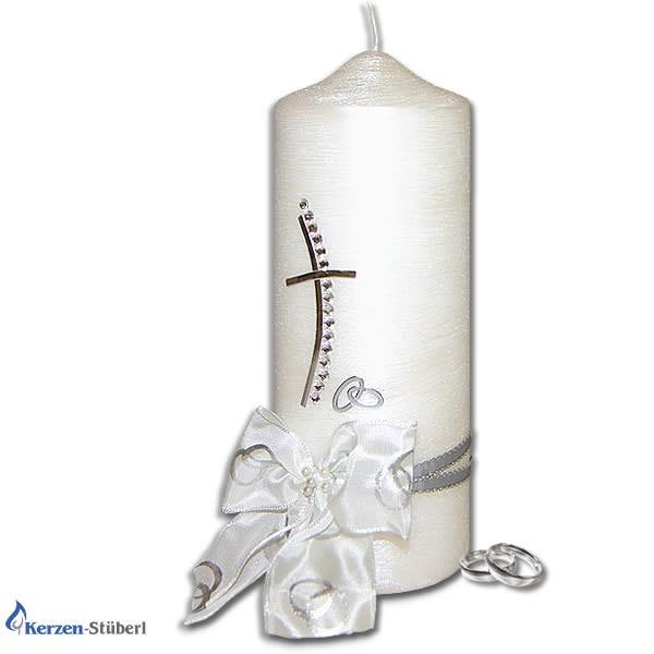 Die Abbildung zeigt eine Hochzeitskerze mit Swarovski-Steinen in Form eines Kreuz. Im unteren Teil der Traukerze befindet sich eine weiße Schleife auf der Trauringe abgebildet sind.